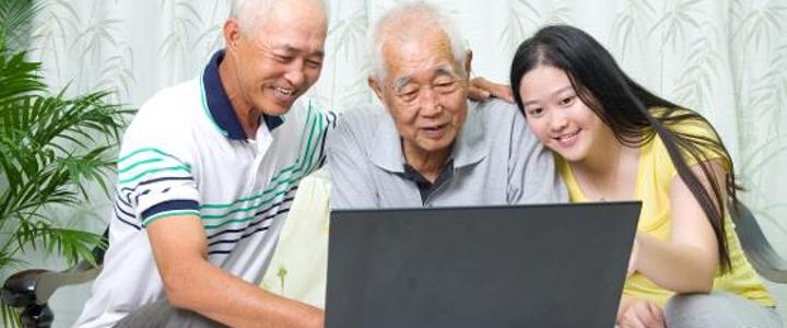 Three people using a laptop