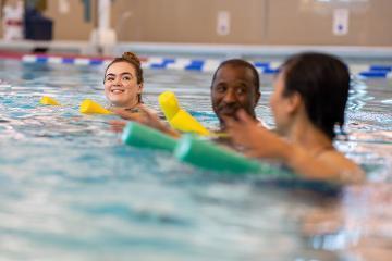Three people in swimming pool