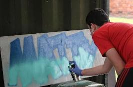 Man using a spray can to create artwork