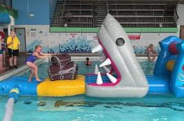 Children playing on an inflatable in a swimming pool